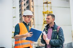 Engineer talking discussing with Architect working with blueprints for architectural plan, sketching a project. Royalty Free Stock Photo