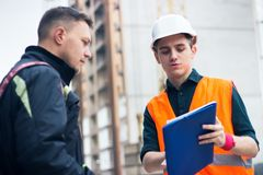 Engineer talking discussing with Architect working with blueprints for architectural plan, sketching a project. Stock Photos