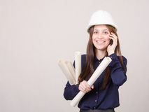 Engineer talking on phone with blueprints in hand Stock Photography