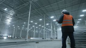 Engineer talking on the phone in new modern industry warehouse.  stock footage