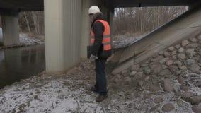 Engineer talking on phone under bridge. In winter day stock footage