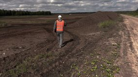 Engineer talking on phone and walk near peat heap
