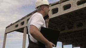 Engineer talking on smart phone near unfinished building. In summer day stock video