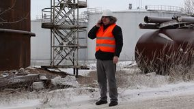 Engineer talking on the smartphone near to the oil tanks stock video footage