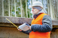 Engineer with tape measure and documentation under the bridge Royalty Free Stock Photo
