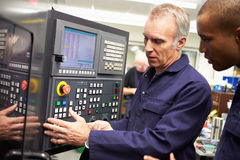 Engineer Teaching Apprentice To Use Computerized Lathe. Having A Discussion stock photography