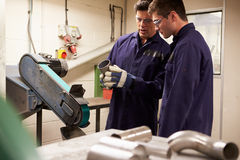 Engineer Teaching Apprentice To Use Grinding Machi stock images