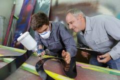 Engineer teaching apprentice to use tig welding machine stock image