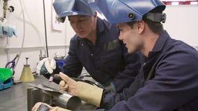 Engineer Teaching Apprentice To Use TIG Welding Machine Royalty Free Stock Image