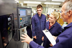 Free Engineer Teaching Apprentices To Use Computerized Lathe Royalty Free Stock Photos - 34159148