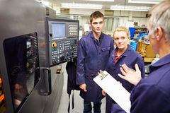 Engineer Teaching Apprentices To Use Computerized Lathe Stock Photo