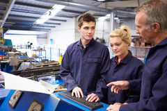 Engineer Teaching Apprentices To Use Tube Bending Machine. Having A Conversation Stock Photography