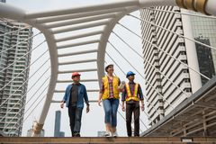 Engineer team at construction site in city. Happy Engineer team of Asian and American engineering officer at constuction site in modern Bangkok city skywalk royalty free stock photos