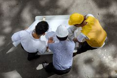 Engineer team discuss project blueprint. Top view of Engineering team of site manager, young field engineer, and foreman look paper blueprint to discuss projet Stock Image