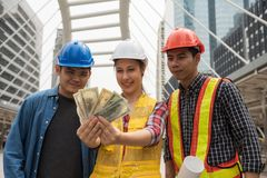 Engineer team look at extra bonus money. Happy engineer team look at extra bonus money, US dollar bills, after construction project complete before due date stock photography