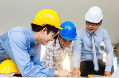 Engineer team looking paper plans at construction site Stock Image