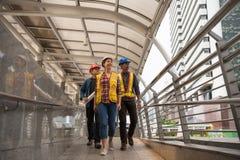 Engineer team walk in city. Happy Engineer team of Asian men and American women walking at Bangkok city skywalk. International group to finish construction stock photos