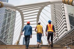 Engineer team walk together. Engineer team of Asian men and American female manager walking on stair of modern Bangkok city skywalk. International joint venture Royalty Free Stock Photography
