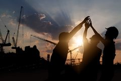 Engineer teamwork, silhouette of construction worker team touching hand together for power at working site.  stock photos