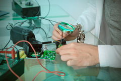 Engineer or tech repairs broken electronic circuit Stock Photography