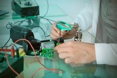 Engineer or tech repairs broken electronic circuit Stock Photography