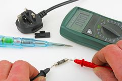 Continuity testing. An engineer testing a fuse with a multimeter stock image