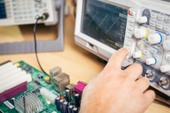 Engineer tests electronic components with oscilloscope in the service center Stock Photo