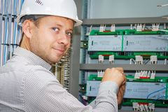 Engineer tests industrial electrical circuits in control terminal box. Electrician adjusts electric equipment in automation panel. Engineer tests industrial Stock Images