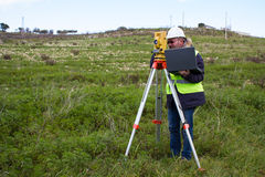 Engineer with theodolite. Engineer in the pipeline controls the project with precision instruments stock photography