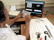 Engineer thinking. Businessman working on a sample tray with the help of auto cad and blueprint engineer thinking about the sample engineer or businessman stock images