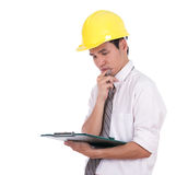 Engineer thinking and looking on clipboard Royalty Free Stock Images