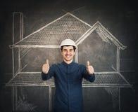 Engineer thumbs up gesture. Happy cheerful young man engineer wearing protective helmet smiling showing thumbs up gesture looking to camera over blackboard stock photo