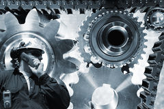 Engineer with titanium and steel gears and cogs. Engineer, mechanic, with giant gears and cogwheels powered by timing chain Royalty Free Stock Photography