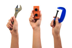 Engineer tool toy concept. Boy hand holding pipe wrench, screw bolt nut and carpenter c-clamp toy tools. Stock Photos