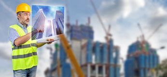Engineer touching skyscraper hologram stock photography