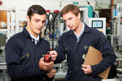 Engineer And Trainee Discussing Component In Factory Stock Photos