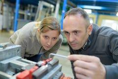 Engineer training female apprentice on milling machine. Female stock image