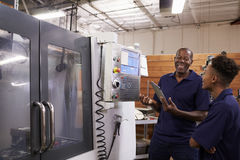 Engineer Training Young Male Apprentice On CNC Machine Royalty Free Stock Photos