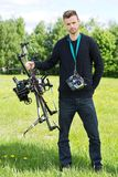 Engineer With UAV Drone And Remote Control. Portrait of young engineer standing with UAV drone and remote control in park stock image