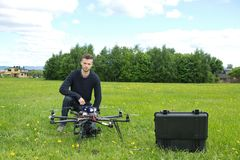 Engineer With UAV Helicopter in Park. Portrait of young engineer with UAV helicopter in park royalty free stock images