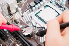 The engineer use multimeter to repairing the motherboard computer. royalty free stock photography