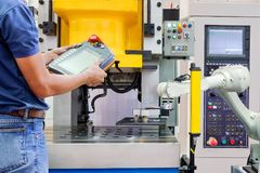 Engineer use wireless remote for control industrial robot working on smart factory. Industry 4.0 concept stock photography