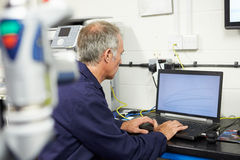 Engineer Using Computerized CMM Arm In Factory. Whilst Sitting Down stock photos