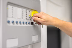 IT Engineer Using Key To Open Fire Panel In Datacenter. Closeup of IT engineer using key to open fire panel in datacenter Stock Photo