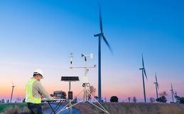 Engineer using laptop computer collect data with meteorological instrument to measure the wind speed, temperature and humidity and. Solar cell system on wind royalty free stock photos