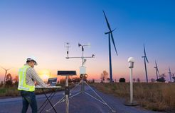 Engineer using laptop computer collect data with meteorological instrument to measure the wind speed, temperature and humidity and. Solar cell system on wind stock image