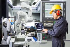 Engineer using computer for maintenance automatic robotic industry Stock Image