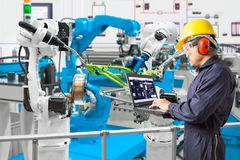 Engineer using laptop computer maintenance automatic robotic. Welding with robot workpiece in automotive industry, Smart factory concept Stock Image