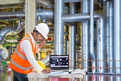 Engineer using laptop computer for maintenance equipment in thermal power plant factory royalty free stock photography