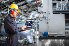 Engineer using laptop computer in thermal power plant factory.  stock photos